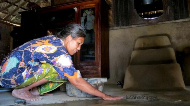 Seorang ibu sedang mengepel lantainya dengan kotoran kerbau yang dicampur dengan air.